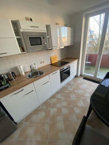 Die Küche mit Zugang zum Balkon
