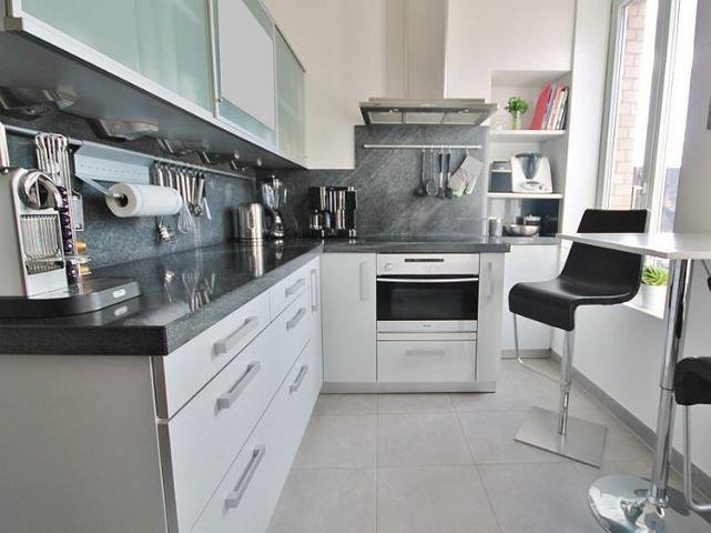 Helle Küche mit weißen Einbauten und Granitarbeits